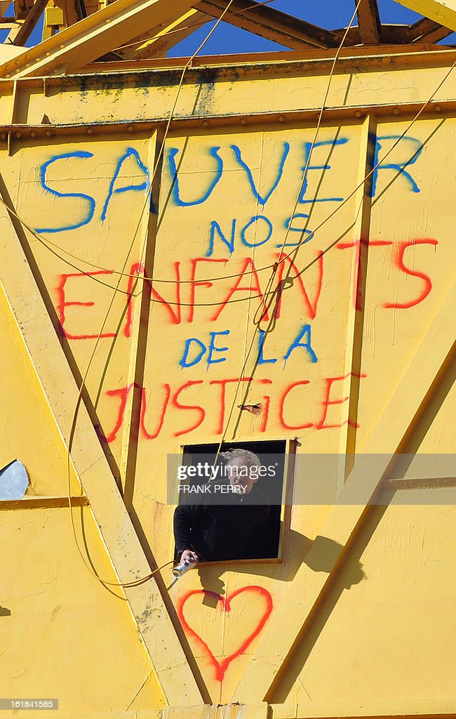 Serge Charnay looks out from a 43-meter crane on February 17, 2013 after spray painting the message ' Save our children from the justice' in Nantes on the third day of a protest for his rights as a father. A second man yesterday climbed another crane in 'an act of solidarity' with Charnay, an action sanctioned by French association 'SOS Papa' indicating that the two men are' victims of family justice in France' .