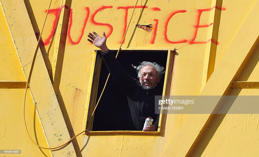 Serge Charnay waves from a 43-meter crane on February 17, 2013 after spray painting the message ' Save our children from the justice' in Nantes on the third day of a protest for his rights as a father. A second man yesterday climbed another crane in 'an act of solidarity' with Charnay, an action sanctioned by French association 'SOS Papa' indicating that the two men are' victims of family justice in France' .