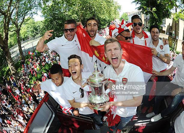 Serge Gnabry Mesut Ozil Lukas Podolski Mathieu Flamini Per Mertesacker Kieran Gibbs Olivier Giroud and Mikel Arteta pose at the Arsenal Victory...