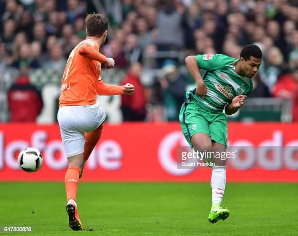 Serge Gnabry of Bremen is challenged by Sandro Sirigu of Darmstadt during the Bundesliga match between Werder Bremen and SV Darmstadt 98 at...