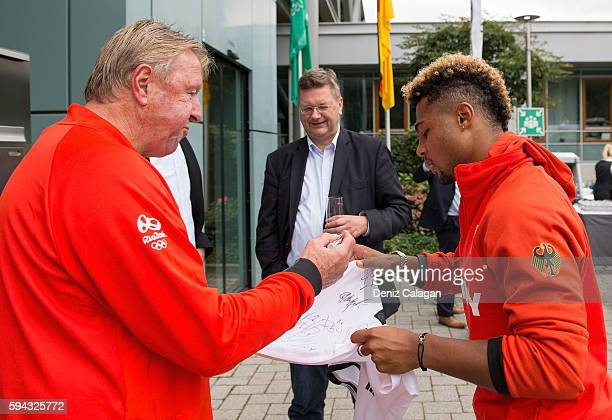 Serge Gnabry receives a pen from head coach Horst Hrubesch to sign a DFB jersey whilst DFB president Reinhard Grindel looks on during the German...