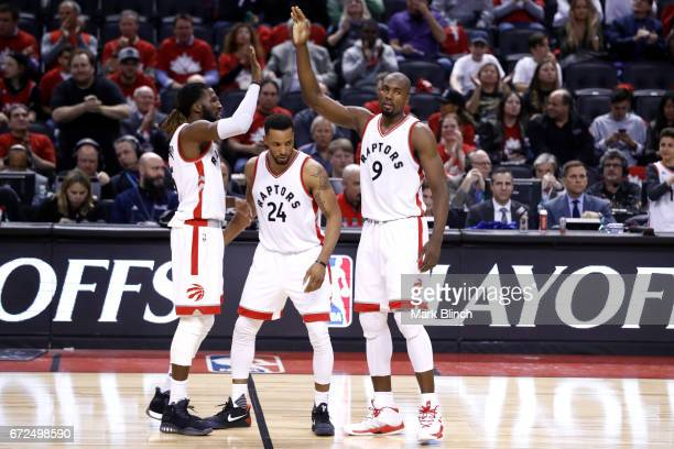 Serge Ibaka and DeMarre Carroll of the Toronto Raptors high five during the game against the Milwaukee Bucks during Game Five of the Eastern...