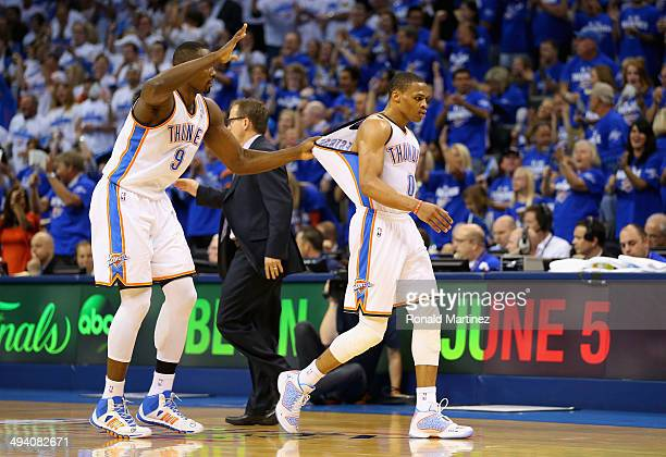 Serge Ibaka and Russell Westbrook of the Oklahoma City Thunder react after a play in the first quarter against the San Antonio Spurs during Game Four...