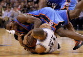 Serge Ibaka of the Oklahoma City Thunder and Tim Duncan of the San Antonio Spurs battle for the ball on the floor in the second quarter in Game Two...