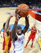 Serge Ibaka of the Oklahoma City Thunder goes for a rebound against Luis Scola of the Houston Rockets during the game at the Oklahoma City Arena on...