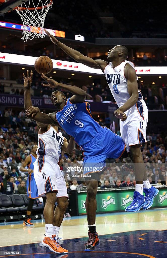 Serge Ibaka of the Oklahoma City Thunder is fouled on his way to the basket by Gerald Henderson and teammate Bismack Biyombo of the Charlotte Bobcats...