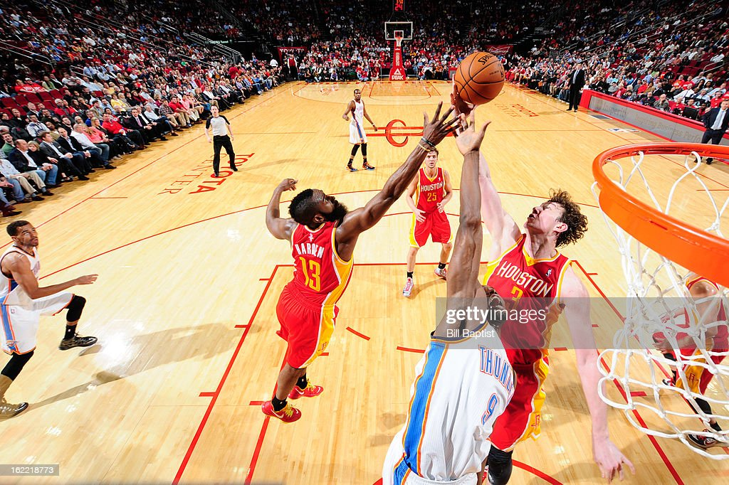 Serge Ibaka #9 of the Oklahoma City Thunder reaches for a rebound against Omer Asik #3 and James Harden #13 of the Houston Rockets on February 20, 2013 at the Toyota Center in Houston, Texas.