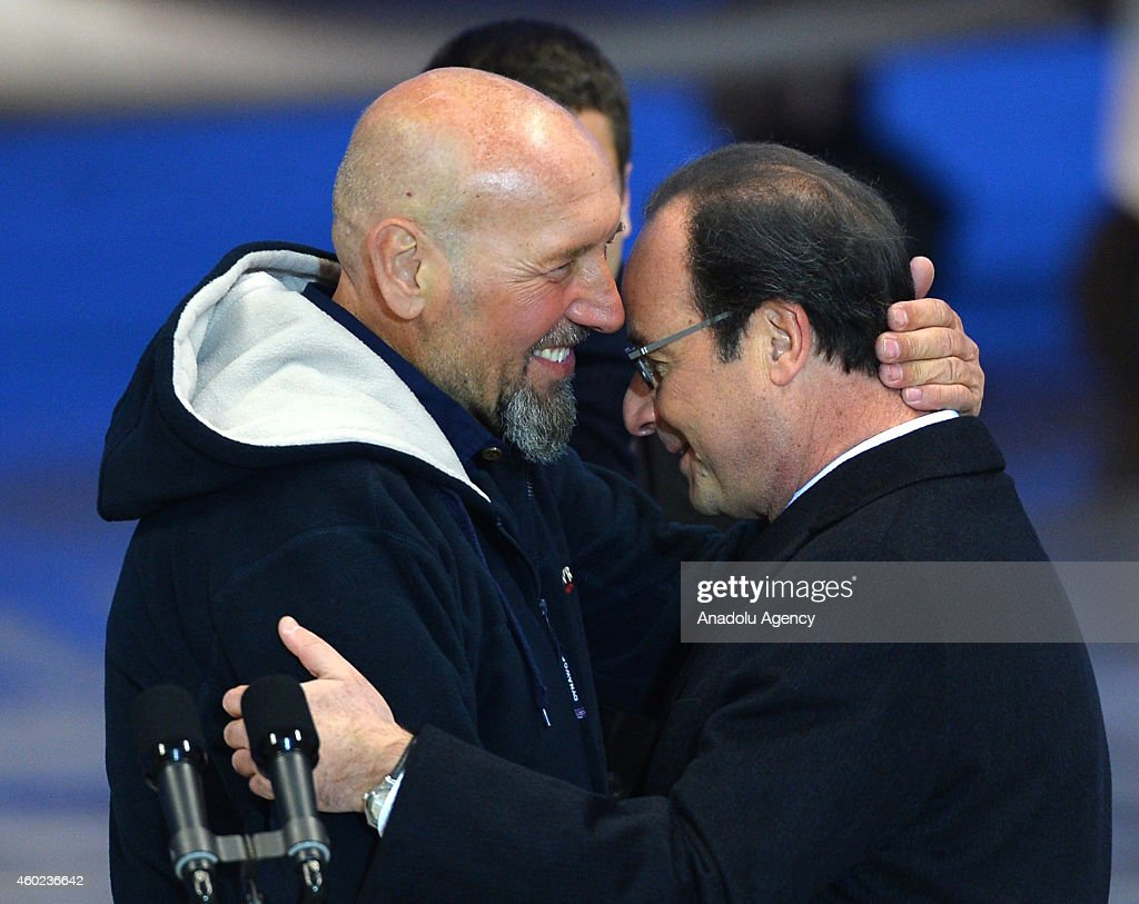 Serge Lazarevic (L), France's last remaining hostage, embraces French President Francois Hollande (R) after landing at the Villacoublay military base near Paris, France on December 10, 2014. Lazarevic, who was snatched by armed men in Mali on November 24, 2011, arrived home on December 10 after three years at the hands of Islamist militants, and was greeted by French President Francois Hollande.