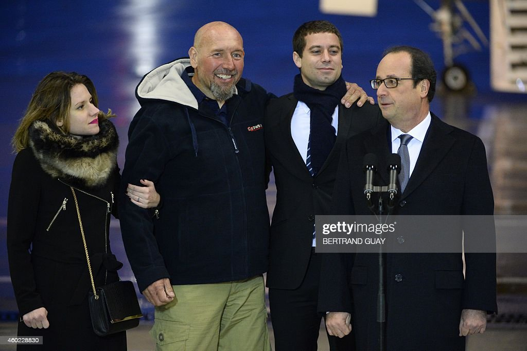 Serge Lazarevic (2nd L), France's last remaining hostage, smiles after landing in a French Republic plane at the Villacoublay military base near Paris on December 10, 2014, as French President Francois Hollande (R) speaks, flanked by Lazarevic's daughter Diane (L) and Clement Verdon (2nd R), son of French executed hostage Philippe Verdon. Lazarevic, who was snatched by armed men in Mali on November 24, 2011, arrived home on December 10 after three years at the hands of Islamist militants, and was greeted by French President Francois Hollande. AFP PHOTO / BERTRAND GUAY