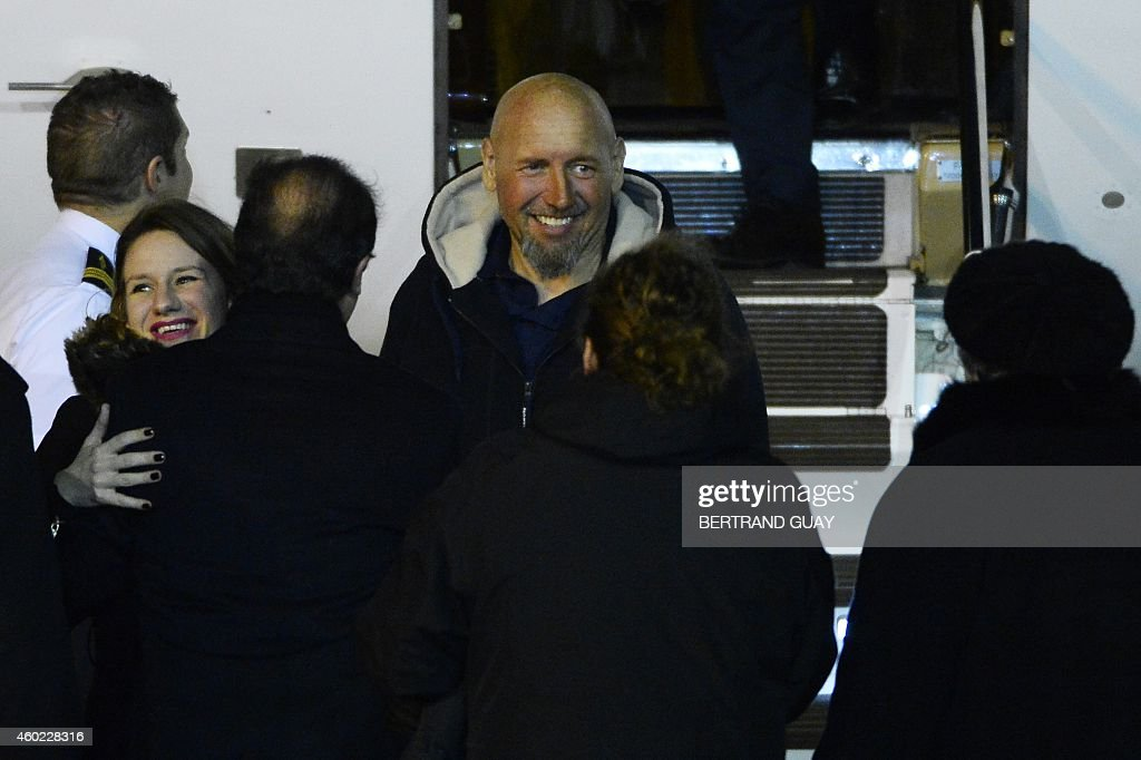 Serge Lazarevic (C), France's last remaining hostage, smiles as his daughter Diane (L) embraces French President Francois Hollande (2nd L), after he landed in a French Republic plane at the Villacoublay military base near Paris on December 10, 2014. Lazarevic, who was snatched by armed men in Mali on November 24, 2011, arrived home on December 10 after three years at the hands of Islamist militants, and was greeted by French President Francois Hollande. AFP PHOTO / BERTRAND GUAY