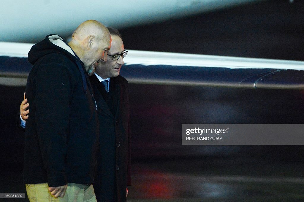 Serge Lazarevic (L), France's last remaining hostage, talks with French President Francois Hollande after Lazarevic landed in a French Republic plane at the Villacoublay military base near Paris on December 10, 2014. Lazarevic, who was snatched by armed men in Mali on November 24, 2011, arrived home on December 10 after three years at the hands of Islamist militants, and was greeted by French President Francois Hollande. AFP PHOTO / BERTRAND GUAY