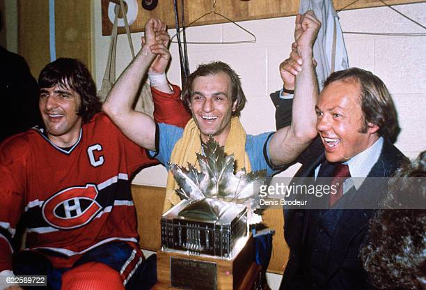 Serge Savard Guy LaFleur and Yvon Cournoyer of the Montreal Canadiens pose in locker room with the Conn Smythe Trophy awarded to LaFleur after...