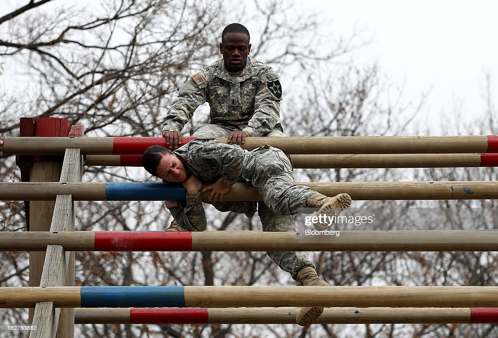 Sergeant Asyah Moore, front, a soldier with the U.S. Army's Second Infantry Division, climbs over an obstacle during an air assault training course at Camp Casey in Dongducheon, South Korea, on Tuesday, Feb. 26, 2013. The U.S. has 28,500 soldiers in South Korea as a legacy of the 1950-53 Korean War, which ended in a cease-fire that left the two Koreas technically still at war. Photographer: SeongJoon Cho/Bloomberg via Getty Images