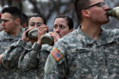 Sergeant Asyah Moore second right a soldier with the US Army's Second Infantry Division takes a drink of water as she stands with other soldiers...