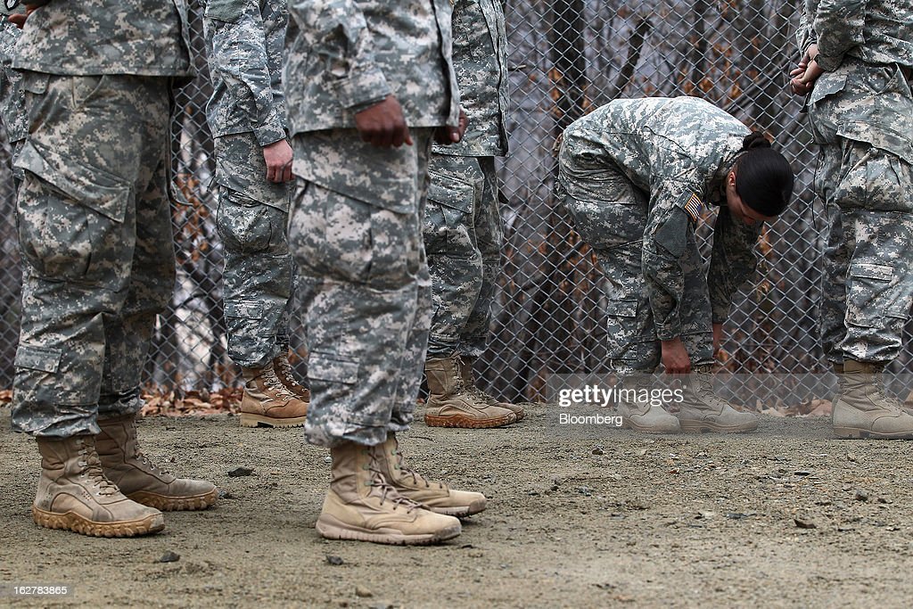 Sergeant Asyah Moore, second right, a soldier with the U.S. Army's Second Infantry Division, checks her shoelaces during an air assault training course at Camp Casey in Dongducheon, South Korea, on Tuesday, Feb. 26, 2013. The U.S. has 28,500 soldiers in South Korea as a legacy of the 1950-53 Korean War, which ended in a cease-fire that left the two Koreas technically still at war. Photographer: SeongJoon Cho/Bloomberg via Getty Images