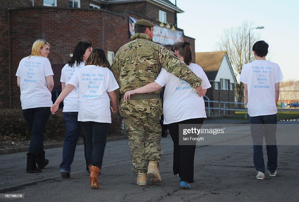 Sergeant Brian Scott walks with his partner Amanda Leghorn as soldiers from Headquarters Company 1st Battalion The Scots Guards return to their base at Bourlon Barracks and are reunited with their families following their recent deployment to Afghanistan on February 27, 2013 in Catterick, England. The soldiers are the first troops from 4 Mechanized Brigade to return to their base from their tour of duty in Afghanistan where they were responsible for the training and mentoring of the Afghan national security forces.