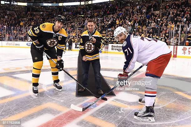 Sergeant Dic Donohue poses with Zdeno Chara of the Boston Bruins and Nick Foligno of the Columbus Blue Jackets for a puck drop before the game at the...