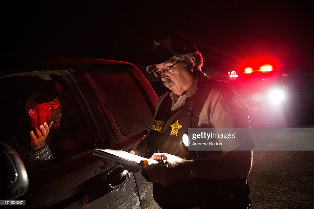 Sergeant Doug Flaten issues a ticket to a man after he ran a stop sign on July 26, 2013 in Williston, North Dakota. The state has seen a rise in crime, automobile accidents and drug usage recently, due in part to the oil boom which has brought tens of thousands of jobs to the region, lowering state unemployment and bringing a surplus to the state budget.