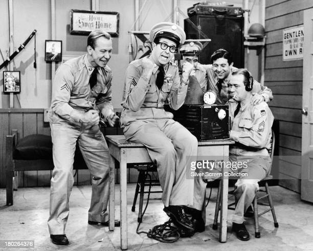 Sergeant Ernie Bilko played by American comedian Phil Silvers and Corporal Steve Henshaw played by Allan Melvin celebrate good news in the US TV...