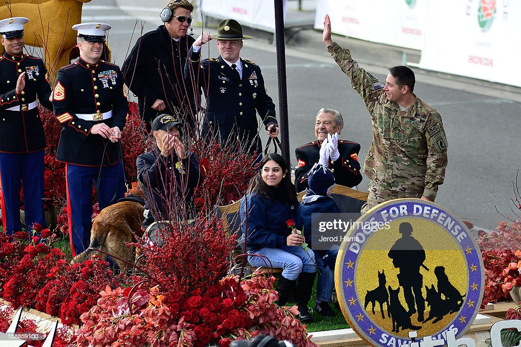 Sergeant First Class Eric Pazz rides the Canines with Courage float after surprising his wife Miriam and son at the 124th annual Rose Parade themed 'Oh, the Places You'll Go!' on January 1, 2013 in Pasadena, California.
