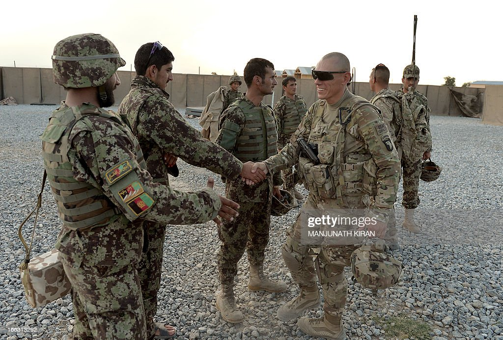 US Sergeant First Class, Hardy (R) of the Field Artillery Battery of 4th Kandak, 4th Brigade, 201st Corps of Combined Team Bastogne (Nangarhar) congratulates soldiers of the Field Artillery Division of the Afghan National Army (ANA) after a training session of ANA soldiers at the US Shinwar Forward Base in the province of Nangarhar on April 11, 2013. The US Field Artillery Battery of 4th Kandak is training Afghan soldiers in using artillery to support their Afghan National Army. AFP PHOTO / MANJUNATH KIRAN