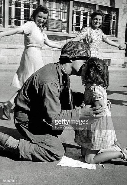 Sergeant Gene Costanzo of the 83rd Infantry Division kneels to kiss a young girl named Noelle while smiling women hold hands and dance around them...