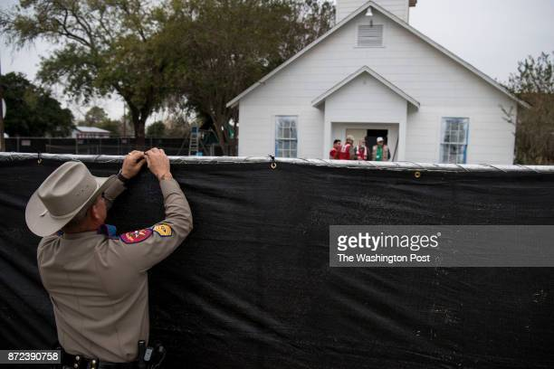 Sergeant John Henke helps put up a black tarp on a fence surrounding the Sutherland Springs First Baptist Church crime scene in Sutherland Springs...