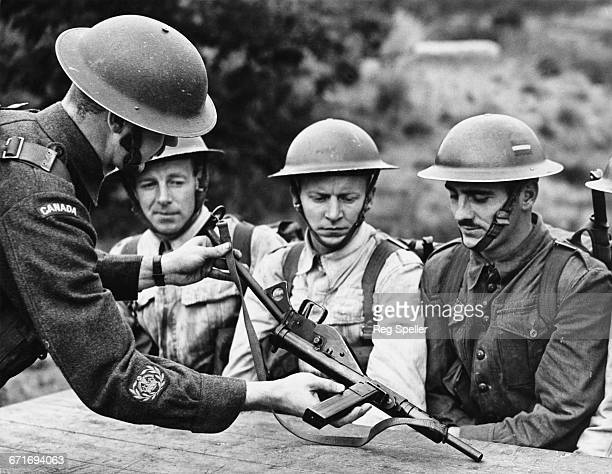 Sergeant Major EH Chevrier from Montreal instructs Canadian army recruits on the use of the Sten Mk II submachine gun on 24 July 1942 at Colchester...