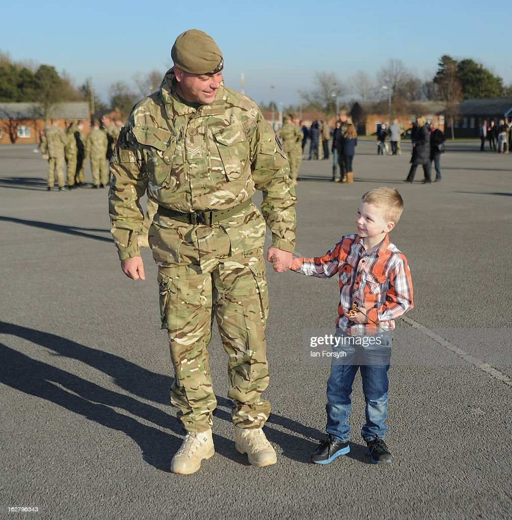 Sergeant Michael Thompson holds the hand of his son, Charlie, 5, as soldiers from Headquarters Company 1st Battalion The Scots Guards return to their base at Bourlon Barracks and are reunited with their families following their recent deployment to Afghanistan on February 27, 2013 in Catterick, England. The soldiers are the first troops from 4 Mechanized Brigade to return to their base from their tour of duty in Afghanistan where they were responsible for the training and mentoring of the Afghan national security forces.