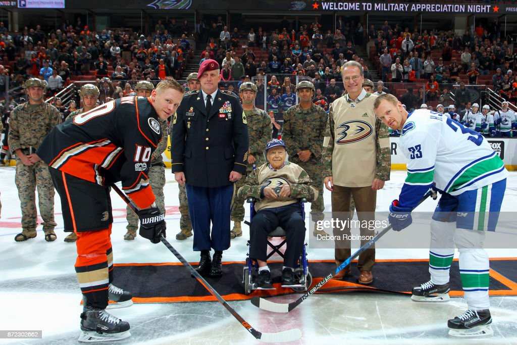 Sergeant Richard Moore, Jr. of the United States Army joins Corey Perry #10 of the Anaheim Ducks, Henrik Sedin #33 of the Vancouver Canucks and Ducks owner Henry Samueli for the honorary puck drop prior to the game on November 9, 2017 at Honda Center in Anaheim, California.