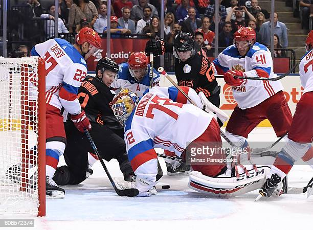 Sergei Bobrovsky of Team Russia scrambles to cover the puck with pressure from Nathan MacKinnon and Ryan NugentHopkins of Team North America during...