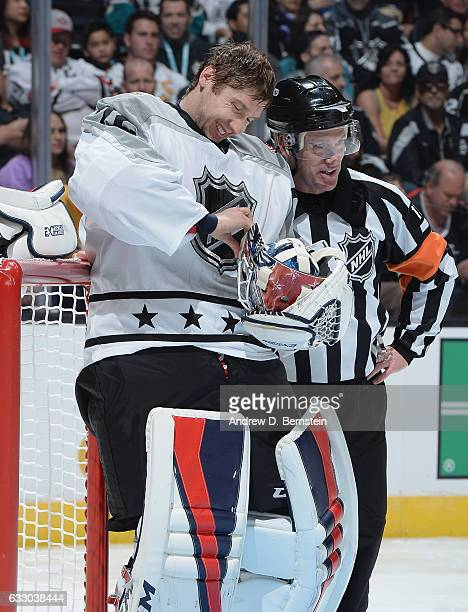Sergei Bobrovsky of the Columbus Blue Jackets adjusts his mask strap as NHL referee Kelly Sutherland looks on during the Metropolitan Division and...