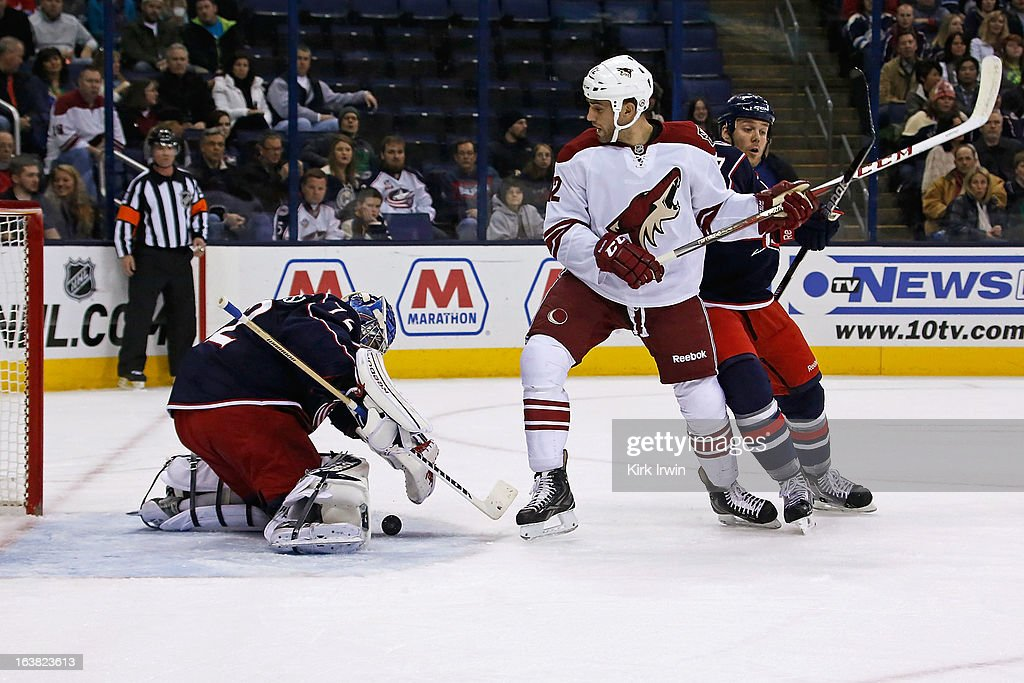 Sergei Bobrovsky #72 of the Columbus Blue Jackets covers up a loose puck as Paul Bissonnette #12 of the Phoenix Coyotes looks for the rebound during the first period on March 16, 2013 at Nationwide Arena in Columbus, Ohio.
