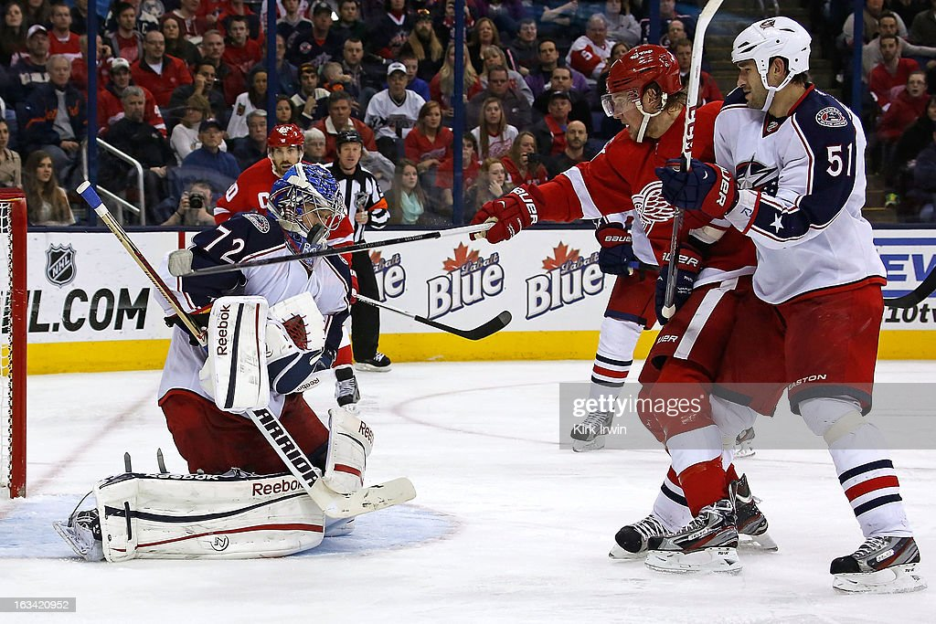 <a gi-track='captionPersonalityLinkClicked' href=/galleries/search?phrase=Sergei+Bobrovsky&family=editorial&specificpeople=4488556 ng-click='$event.stopPropagation()'>Sergei Bobrovsky</a> #72 of the Columbus Blue Jackets makes a save as <a gi-track='captionPersonalityLinkClicked' href=/galleries/search?phrase=Justin+Abdelkader&family=editorial&specificpeople=2271858 ng-click='$event.stopPropagation()'>Justin Abdelkader</a> #8 of the Detroit Red Wings reaches out for the puck as he is checked by <a gi-track='captionPersonalityLinkClicked' href=/galleries/search?phrase=Fedor+Tyutin&family=editorial&specificpeople=215245 ng-click='$event.stopPropagation()'>Fedor Tyutin</a> #51 of the Columbus Blue Jackets during the third period on March 9, 2013 at Nationwide Arena in Columbus, Ohio. Bobrovsky had 30 saves as Columbus defeated Detroit 3-0.