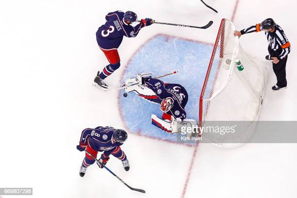 Sergei Bobrovsky of the Columbus Blue Jackets makes a save while Seth Jones of the Columbus Blue Jackets and Zach Werenski of the Columbus Blue...