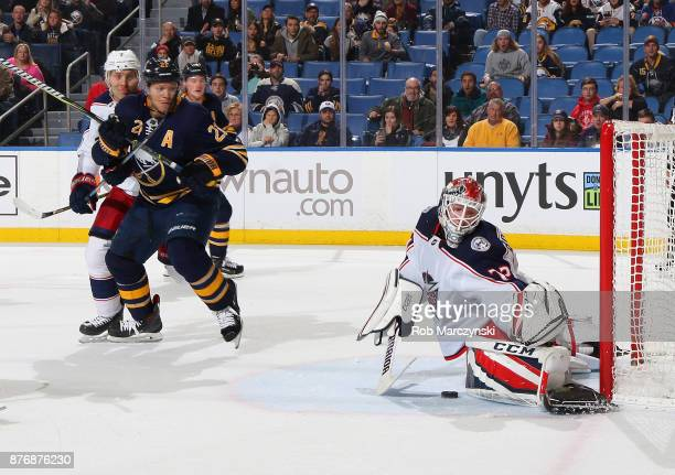Sergei Bobrovsky of the Columbus Blue Jackets makes a third period save as Kyle Okposo of the Buffalo Sabres looks for a rebound during an NHL game...