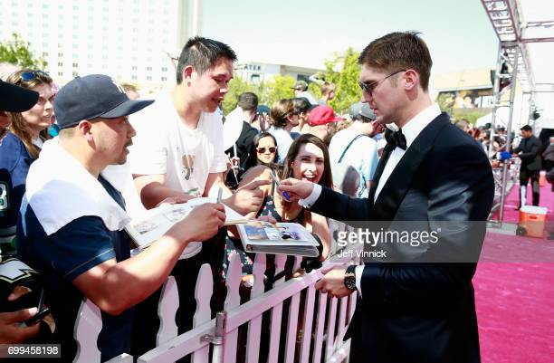 Sergei Bobrovsky of the Columbus Blue Jackets signs an autograph as he arrives on the magenta carpet for the 2017 NHL Awards at TMobile Arena on June...