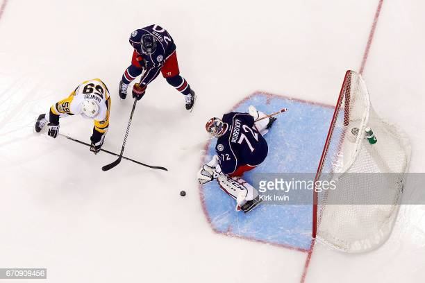 Sergei Bobrovsky of the Columbus Blue Jackets stops a shot from Jake Guentzel of the Pittsburgh Penguins as Brandon Saad of the Columbus Blue Jackets...