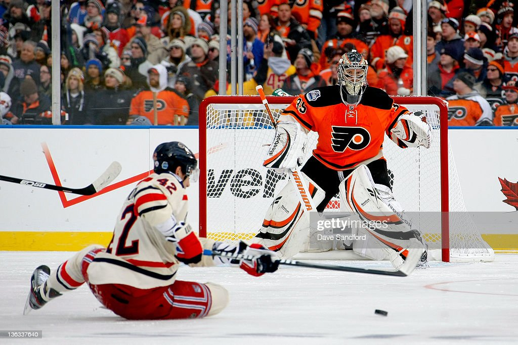 Sergei Bobrovsky of the Philadelphia Flyers defends the net as Artem Anisimov of the New York Rangers falls to the ice trying to control the puck...
