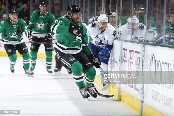 Sergei Gonchar of the Dallas Stars tries to track down the loose puck against Brad Richardson of the Vancouver Canucks at the American Airlines...