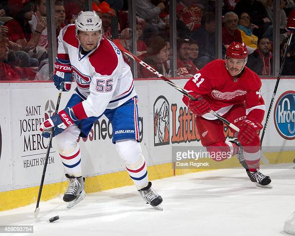 Sergei Gonchar of the Montreal Canadiens skates with the puck as Luke Glendening of the Detroit Red Wings pressures him behind the net during a NHL...