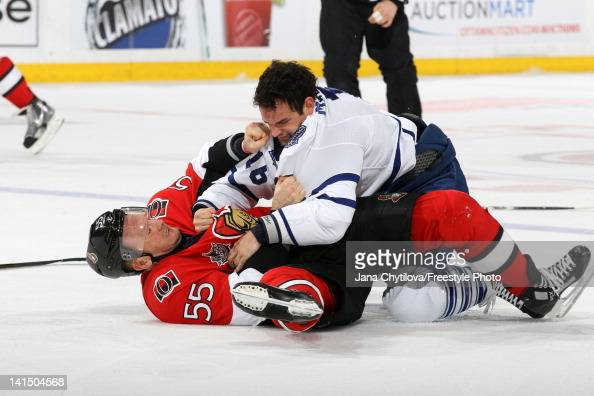 Sergei Gonchar of the Ottawa Senators falls to the ice in a fight against Clarke MacArthur of the Toronto Maple Leafs during an NHL game at...