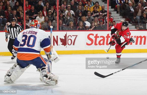 Sergei Gonchar of the Ottawa Senators shoots the puck scoring the opening goal of the game against Dwayne Roloson of the New York Islanders at...