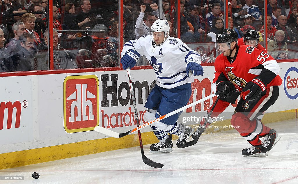 Sergei Gonchar #55 of the Ottawa Senators skates for the loose puck against Jay McClement #11 of the Toronto Maple Leafs during an NHL game at Scotiabank Place on February 23, 2013 in Ottawa, Ontario, Canada.