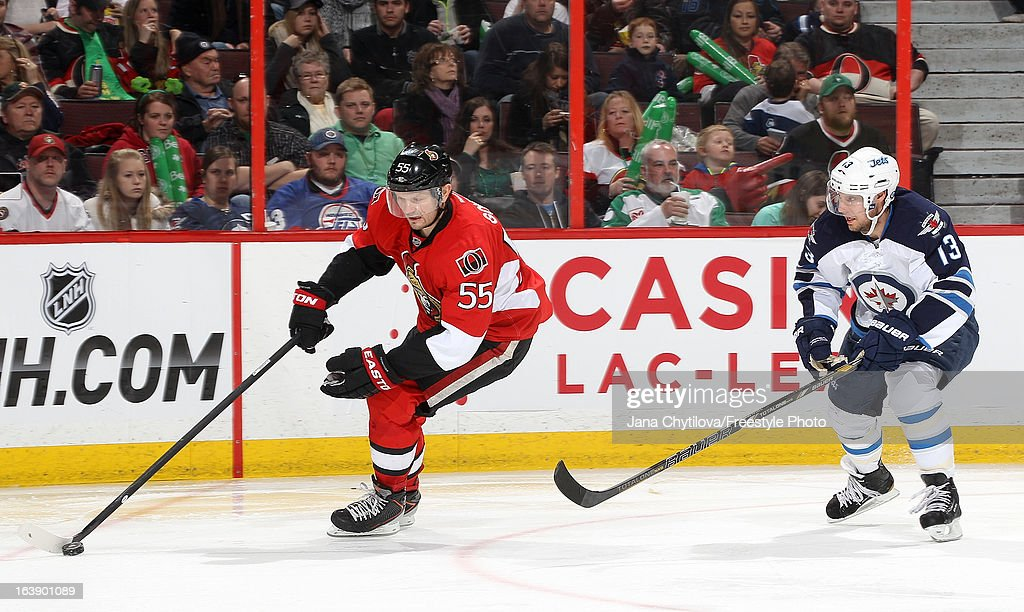 <a gi-track='captionPersonalityLinkClicked' href=/galleries/search?phrase=Sergei+Gonchar&family=editorial&specificpeople=202470 ng-click='$event.stopPropagation()'>Sergei Gonchar</a> #55 of the Ottawa Senators skates with the puck while being chased by <a gi-track='captionPersonalityLinkClicked' href=/galleries/search?phrase=Kyle+Wellwood&family=editorial&specificpeople=577984 ng-click='$event.stopPropagation()'>Kyle Wellwood</a> #13 of the Winnipeg Jets, during an NHL game at Scotiabank Place, on March 17, 2013 in Ottawa, Ontario, Canada.