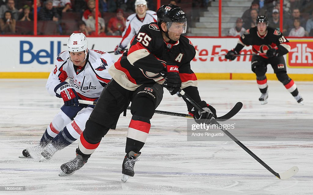 Sergei Gonchar #55 of the Ottawa Senators spins to stickhandle the puck away from Matt Hendricks #26 of the Washington Capitals on January 29, 2013 at Scotiabank Place in Ottawa, Ontario, Canada.