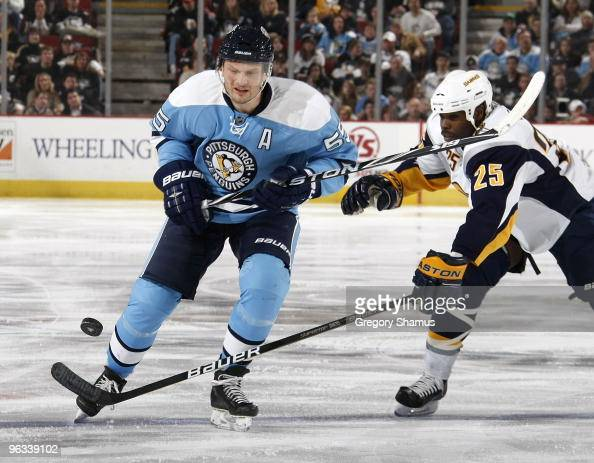 Sergei Gonchar of the Pittsburgh Penguins battles for the puck against Michael Grier of the Buffalo Sabres on February 1 2010 at Mellon Arena in...
