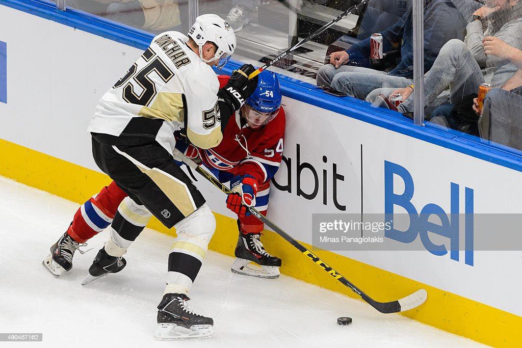 Sergei Gonchar #55 of the Pittsburgh Penguins checks Charles Hudon #54 of the Montreal Canadiens against the boards during the NHL pre-season game at the Videotron Centre on September 28, 2015 in Quebec City, Quebec, Canada.