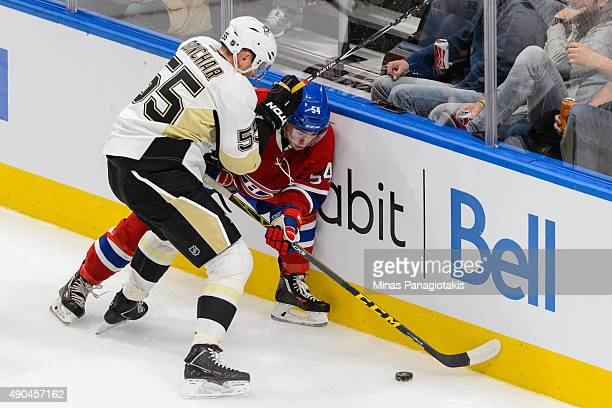 Sergei Gonchar of the Pittsburgh Penguins checks Charles Hudon of the Montreal Canadiens against the boards during the NHL preseason game at the...