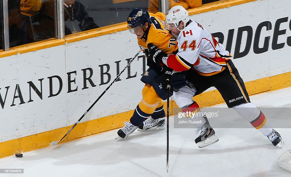 Sergei Kostitsyn #74 of the Nashville Predators battles along the boards against Chris Butler #44 of the Calgary Flames during an NHL game at the Bridgestone Arena on April 23, 2013 in Nashville, Tennessee.